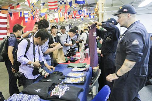 Khách tham quan mua đồ lưu niệm trên tàu sân bay. Ảnh: Nguyễn Đông.