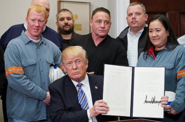 Tổng thống Mỹ Donald Trump ký thông qua đạo luật áp thuế với nhôm, thép nhập khẩu tại Nhà Trắng ngày 8/3. Ảnh: AFP.