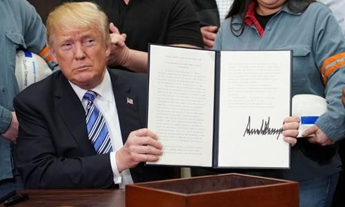 Tổng thống Donald Trump ký lệnh áp thuế nhập khẩu nhôm, thép tại Nhà Trắng ngày 8/3. Ảnh: AFP.