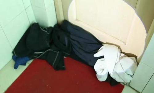 Khe cửa nhà vệ sinh bị chặn bằng nhiều quần áo.