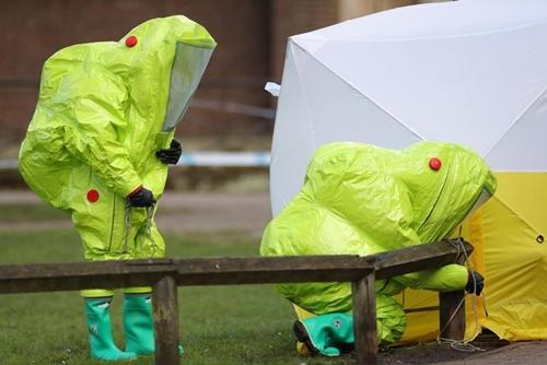 Các nhân viên mặc đồ chống độc làm việc để đảm bảo an toàn khu lều bao phủ ghế băng ở trung tâm thương mại tại Salisbury hôm 8/3. Đây là nơi Skripal và con gái được tìm thấy trong tình trạng nguy cấp do phơi nhiễm chất độc thần kinh. Ảnh: AP.