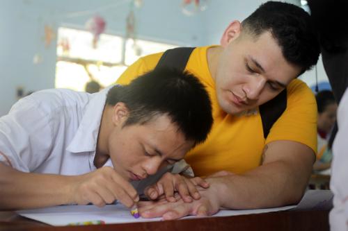 Em Lý Lâm Phong đặt bàn tay thủy thủ Mỹ để vẽ theo. Ảnh: Nguyễn Đông.