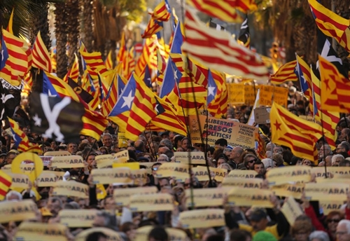 Demonstrators wave Catalan pro independence Estelada flags as they protest to demand a Catalan republic, called by the pro-independence Catalan National Assembly (ANC) citizens group in Barcelona on March 11, 2018. Tens of thousands of Catalans demonstrated in Barcelona today to demand unity to separatist political parties to form a government and implement the republic they declared in October but could not deploy due to the Spanish government intervention.