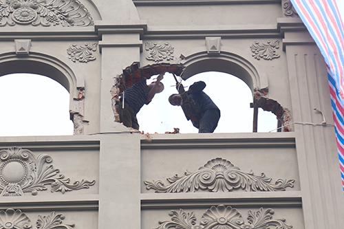 Công nhân đang phá dỡ phần sai phạm ơ tầng năm căn nhà. Ảnh: Phạm Dự.