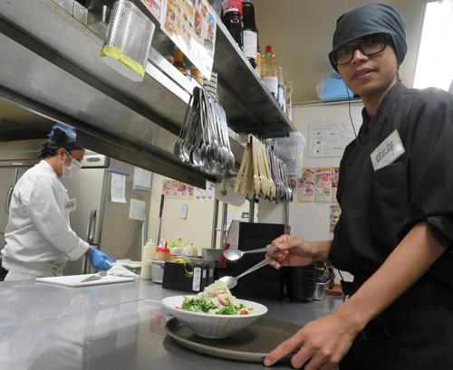 Một lao động người Việt Nam (phải) chuẩn bị món ăn trong bếp của nhà hàngAmataro ởNagoya, Nhật Bản. Ảnh:Chunichi Shimbun.