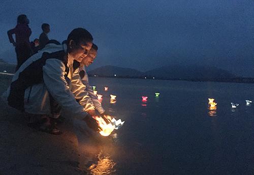 Cựu binh, người thân liệt sĩ Gạc Ma thả đèn hoa đăng tối 12/3 ở cửa biển Cẩm Nhượng. Ảnh: Đức Hùng