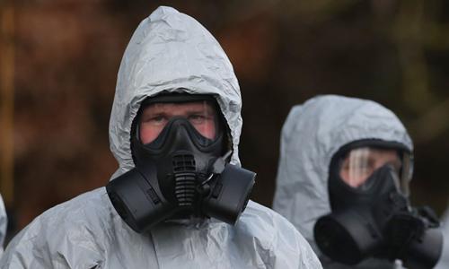 Chuyên viên phòng hóa Anh thu thập dấu vết chất độc tại hiện trường. Ảnh: AFP.