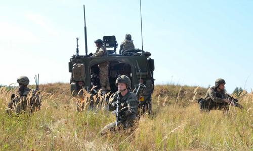 Lính Mỹ triển khai đội hình tam giác với sự yểm trợ của xe thiết giápkhi tuần tra. Ảnh: US Army.