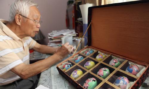 Ông Fei miệt mài sáng tạo nghệ thuật trên vỏ trứng. Ảnh: VCG.