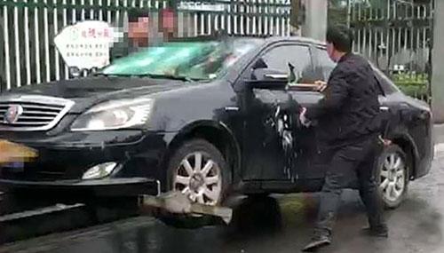 Tài xế bất ngờ dùng búa đập phá chính ôtô của mình khi cảnh sát chuẩn bị kéo xe đi. Ảnh: The Paper.