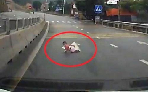 Hình ảnh cháu bé bò trên quốc lộ 18A ở Quảng Ninh. Ảnh: Cắt từ Clip