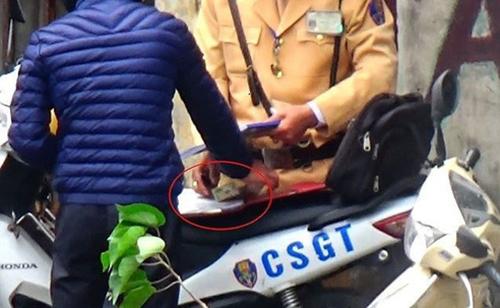 Hình ảnh cảnh sát giao thông nghi nhận tiền người vi phạm bị ghi lại.Ảnh: Cắt từ video.