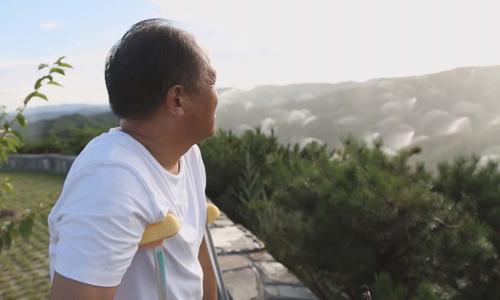 Ông Zhang quan sát hệ thống tưới nước trồng cây gây rừng. Ảnh: CGTN.