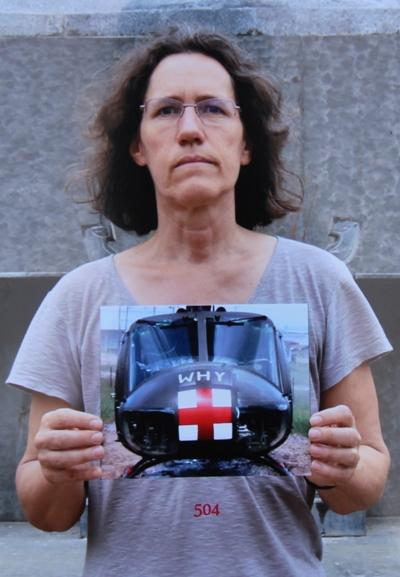 Người phụ nữ cầm bức ảnh chiếc trực thăng với chữ Why do Mike chụp gần 50 năm trước. Ảnh: Phạm Linh.
