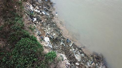 Trước đó không lâu, một tàu hút cát trái phép đã đã làm sạt lở bãi bồi, để lộ ra chân bãi rác này nhưng không được nhà chức trách lưu tâm. Ảnh: Giang Chinh