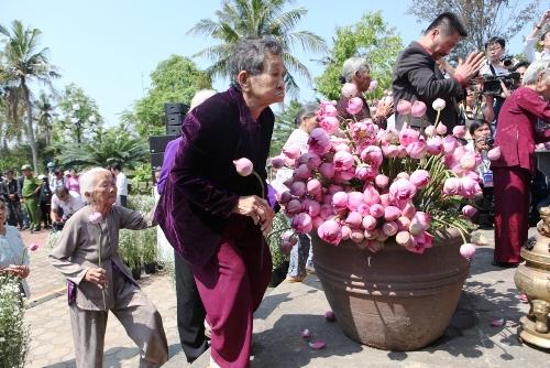 Những nạn nhân sống sót bồi hồi khi dâng hoa sen lên những người thân đã mất 50 năm trước. Ảnh: Phạm Linh.