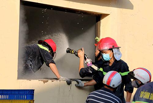 Cảnh sát chữa cháy phun nước khống chế ngọn lửa. Ảnh: Phước Tuấn