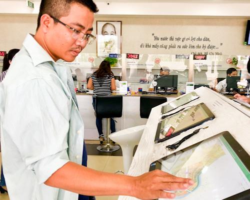 Người dân sử dụng các ứng dụng thông minh tại UBND quận 12. Ảnh: Tuyết Nguyễn.