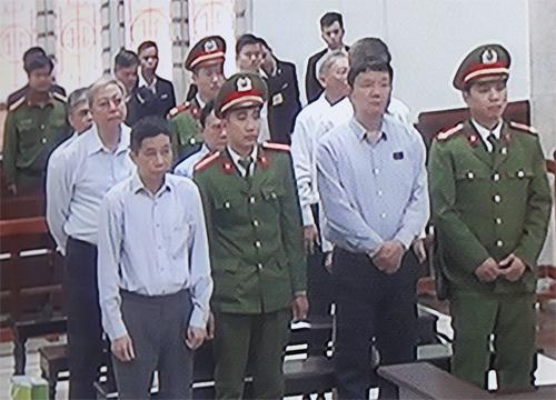 Bảy bị cáo tại phiên tòa, ông Đinh La Thăng đứng ở hàng ghế đầu. Ảnh chụp qua màn hình