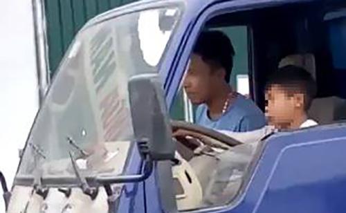 Bé trai cầm lái xe tải. Ảnh cắt từ video.