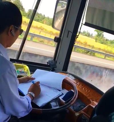 Tài xế vừa lái xe vừa ghi sổ sách. Ảnh: Cắt từ video
