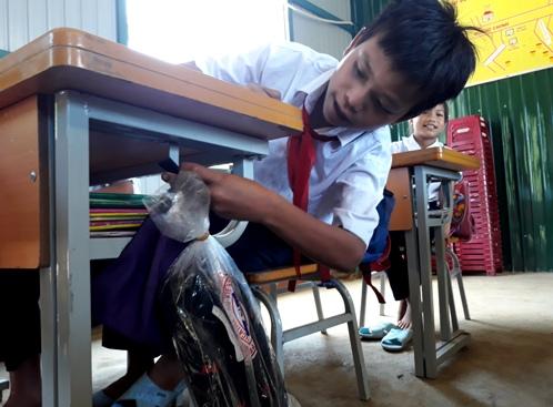 Các học sinh trường tiểu học Trà Nham vui mừng khi được tặng dép mới. Ảnh: Hà Xuyên.