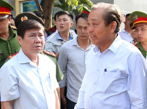 Ông Trương Hòa Bình (phải) kiểm tra công tác khắc phục hậu quả tại chung cư Carina. Ảnh: Mạnh Tùng.