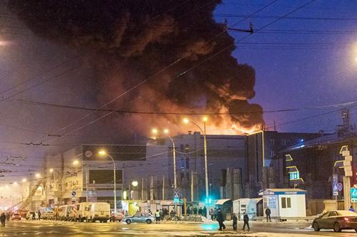Lửa khói nghi ngút bốc lên từtrung tâm thương mại Winter Cherry tại thành phố Kemerovo, Tây Siberia, Nga. Ảnh: TASS