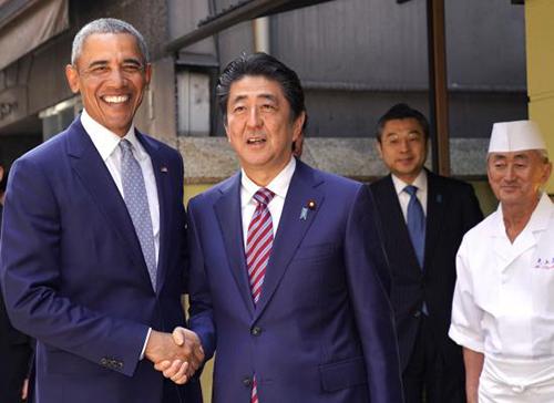 Ông Obama và ông Abe bắt tay trước khi vào ăn sushi ở một nhà hàng Tokyo hôm qua. Ảnh: AFP