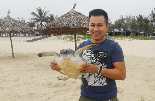 Anh Hồ Nhật Tân thả cá thể rùa về biển.Ảnh: Đắc Thành.