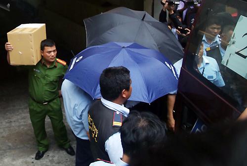 Cảnh sát đưa hai nghi can và tài liệu chứng từ đi. Ảnh: Quốc Thắng.