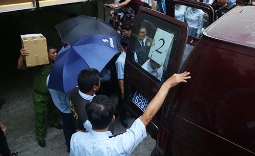 Cảnh sát đưa hai nghi can và tài liệu chứng từ đi,. Ảnh: Quốc Thắng.