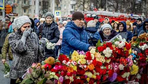 Người dân đặt hoa tưởng niệm các nạn nhân ở trung tâm thương mại Winter Cherry. Ảnh: AFP