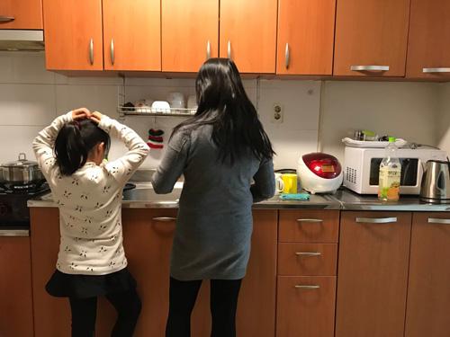 Vợ người đánh cá và cô con gái 8 tuổi đứng làm bếp tại căn hộ hai buồng ngủ ven đô Seoul, Hàn Quốc. Ảnh: Washington Post.