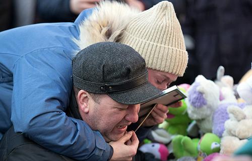 Người thân đau đớn khóc ở góc tưởng niệm các nạn nhân thiệt mạng tại Winter Cherry. Ảnh: TASS