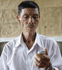 Ông Nam phải dùng máy trợ thính khi trò chuyện với người khác. Ảnh: Nguyễn Hải.