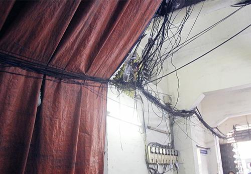 Bạt, dây điện chằng chịt dưới hầm giữ xe chung cư Nguyễn Thị Nghĩa. Ảnh: Duy Trần
