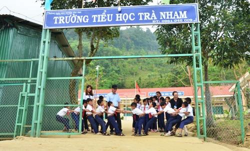 Các học sinh tiểu học Trà Nham chơi kéo co trước cổng trường. Ảnh: Phạm Linh.