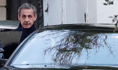Cựu tổng thống PhápNicolas Sarkozy ra khỏi nhà riêng ở Paris vào ngày 21/3. Ảnh: Reuters.