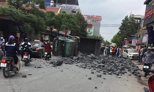 Xe tải lật ngang giữa đường, đá đổ khắp nơi.