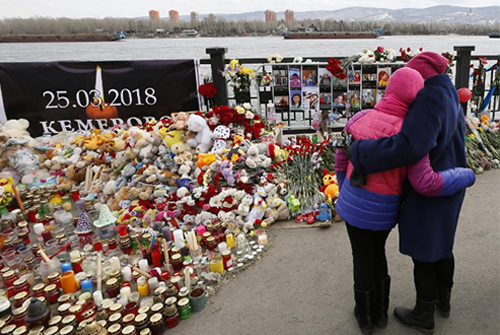 People visit a makeshift memorial on the day of national mourning for the victims of a shopping mall fire in Kemerovo on an embankment of the Yenisei River in the Siberian city of Krasnoyarsk, Russia March 28, 2018. REUTERS/Ilya Naymushin/File Photo