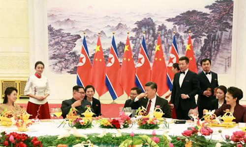 [Caption]Xi Jinping drinks a glass of baijiu as Kim Jong-un looks onCREDIT:KCNA/AFP