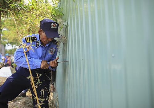 Bảo vệ của Công ty Trung Thủy tháo dỡ hàng rào tôn bịt kín khu dân cư với biển. Ảnh: Nguyễn Đông.