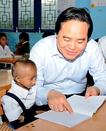 Bộ trưởng Giáo dục và Đào tạo Phùng Xuân Nhạ dạy đọc chữ cái cho học trò Đinh Văn KRể. Ảnh: Bá Hải.