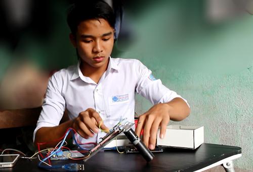 Em Nguyễn Văn Sỹ lắp ráp các thiết bị.Ảnh: Đắc Thành.