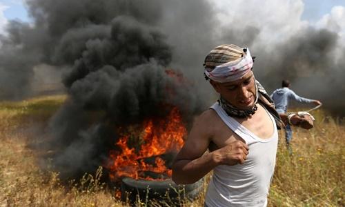 Một thanh niên Palestine tham gia cuộc biểu tình ở biên giới Israel và Gaza ngày 30/3. Ảnh: Reuters.