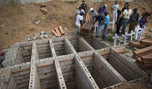 Một ngôi mộ tập thể chôn cất các nạn nhân chết cháy trong vụ bạo loạn tại một đồn cảnh sát ở Venezuela xảy ra vào ngày 28/3. Ảnh: AP.