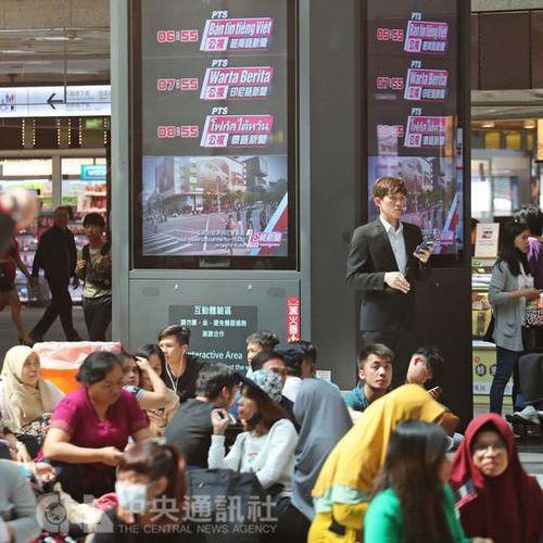 Người dân ngồi cạnh bảng quảng cáo các chương trình tin tức mới của PTS ở ga tàu Đài Bắc. Ảnh: CNA