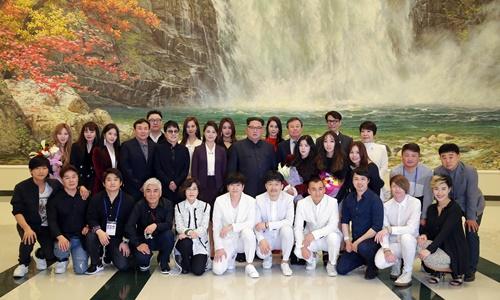 Ông Kim Jong-un và vợ chụp ảnh cùng các nghệ sĩ Hàn Quốc. Ảnh: Reuters.