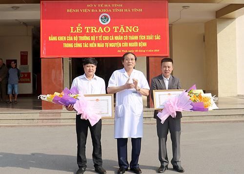 Giám đốc Bệnh viện Đa khoa Hà Tĩnh (giữa) tặng bằng khen cho hai anh Quân và Hùng. Ảnh: Đức Hùng